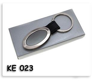 พวงกุญแจโลหะรูปวงรีเชื่อมด้วยแผ่นหนังพร้อมสกรีนโลโก้บรรจุในกล่องกระดาษดูดี