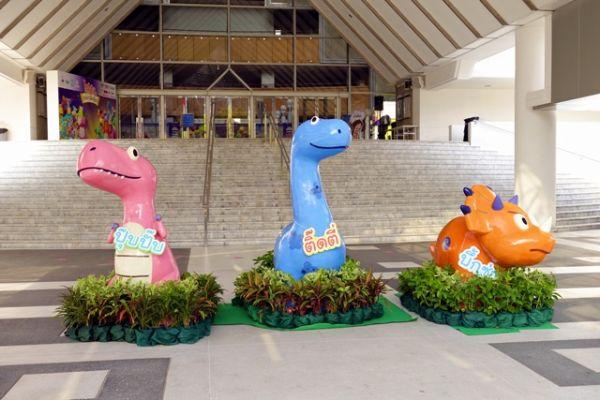 รูปปั้นของไดโนเสาร์สีสดใสที่นำมาจัดแสดงว่าหน้าประตูหอประชุม