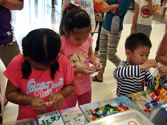 น้องๆ กำลังสนุกสนานกับการเล่นตัวต่อแบบต่างๆ ทั้งลาคิว อโซบล็อค และ จิเอโบะ ที่บูธของฮายาชิเวิดล์