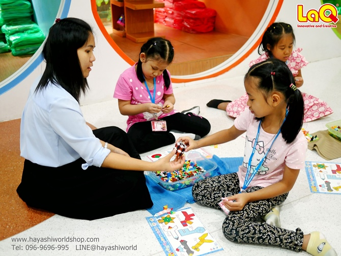 คุณครูกำลังช่วยแนะนำให้เด็กๆ เรียนรู็วิธีการต่อลาคิว