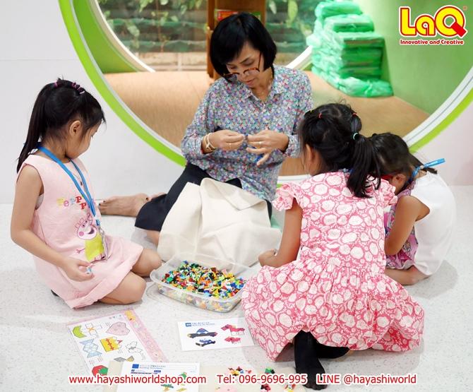 คุณครูกำลังช่วยสอนให้เด็กๆ ได้รู้วิธีการเล่นตัวต่อลาคิว