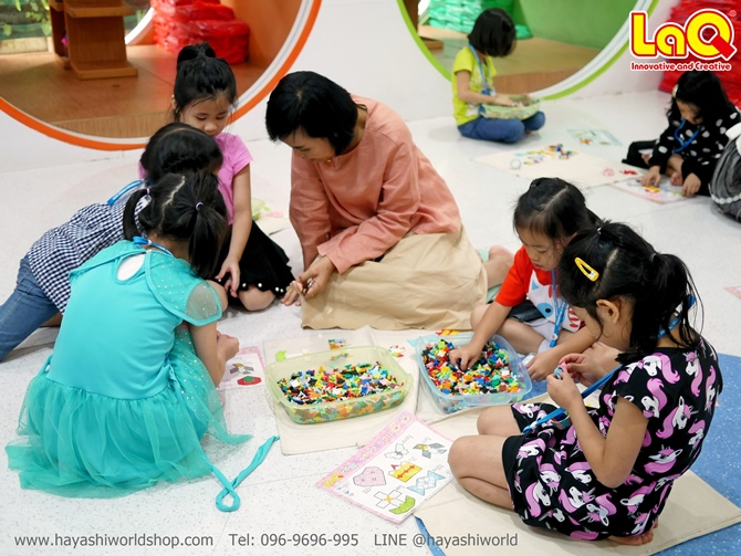 คุณครูกำลังช่วยสอนวิธีการต่อลาคิว LaQ ให้กับเด็กๆ ในห้อง
