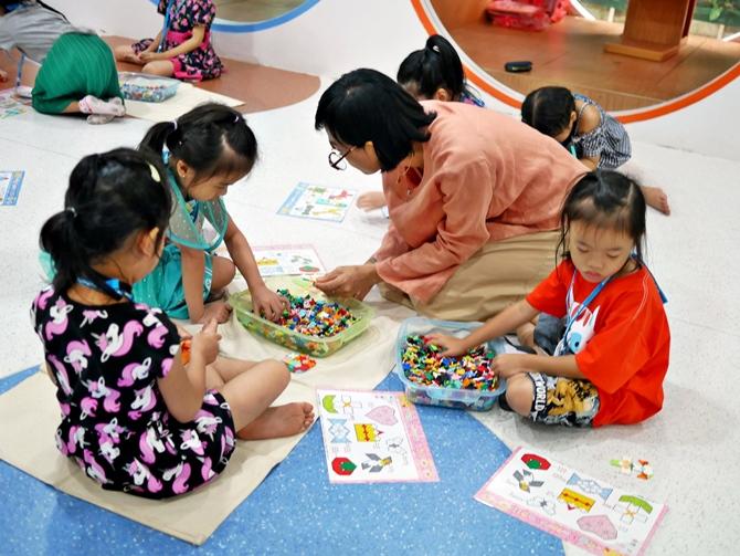 คุณครูมาช่วยสอนเด็กๆ เรียนรู้วิธีการเล่นตัวต่อลาคิวด้วย
