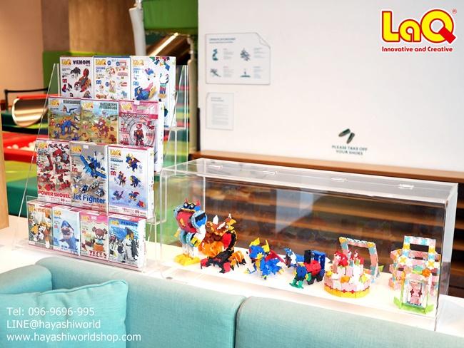 ชั้นวางแสดงสินค้าบางส่วนของตัวต่อเสริมทักษะ ลาคิว LaQ จากญี่ปุ่น โดยมีตู้โชว์โมเดลของลาคิววางอยู่ข้างๆ